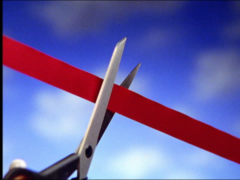 """zoom in large scissors cutting """"red tape"""" with blue studio background - ribbon sewing item stock videos & royalty-free footage"""