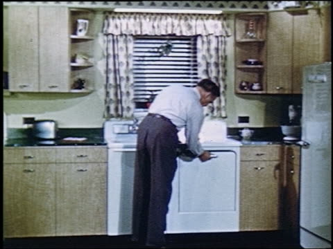 1952 zoom in man loading up dishwasher in kitchen + turning it on / wife enters + he kisses her - 1952 stock videos & royalty-free footage