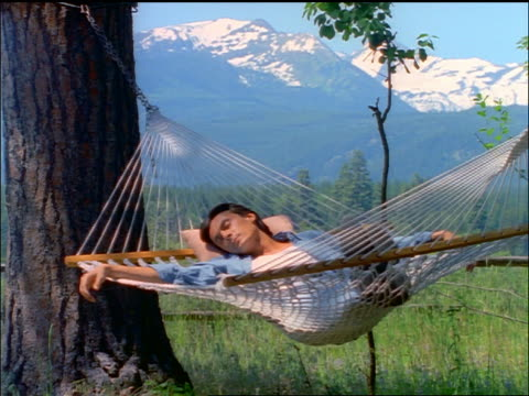zoom in man napping in hammock / mountains in background / montana - wasting time stock videos & royalty-free footage