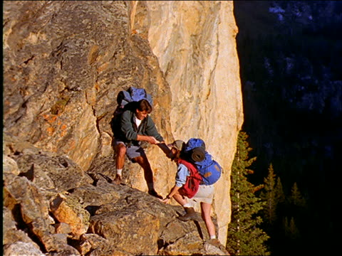 zoom in man with backpack helps woman climb onto rock / they hug - paar mittleren alters stock-videos und b-roll-filmmaterial
