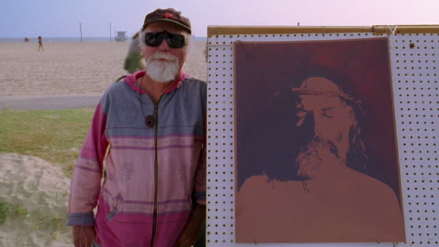 Zoom in medium shot elderly man posing next to paintings with people on bicycle path and beach in background / Venice Beach