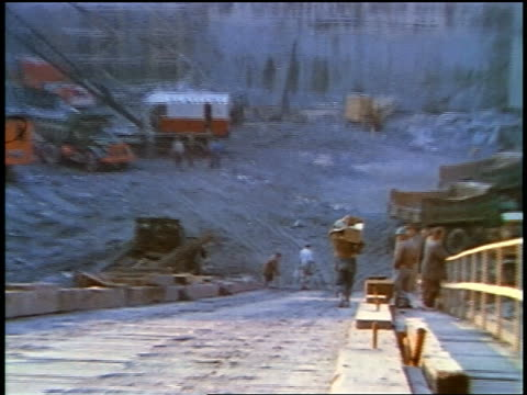 1957 zoom in men walking down slope of large construction site - anno 1957 video stock e b–roll