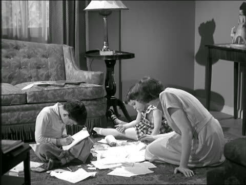 b/w 1950 zoom in mother with daughter + son drawing on living room floor / daughter shows mother drawing - homework stock videos & royalty-free footage