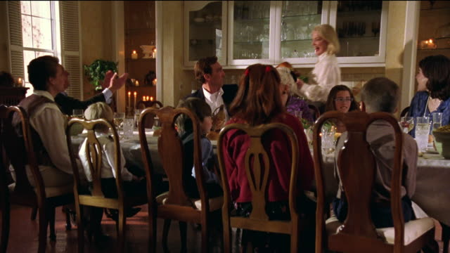 zoom in multi-generational family sitting at dining room table eating dinner with woman bringing in turkey - dining room stock videos & royalty-free footage