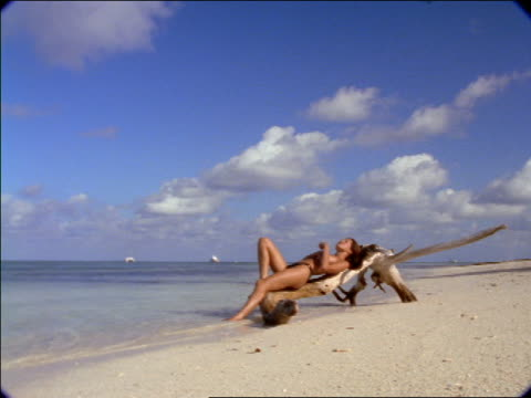 zoom in nude woman lying on large driftwood on beach cupping water into hand + onto body / seychelles - costume intero video stock e b–roll