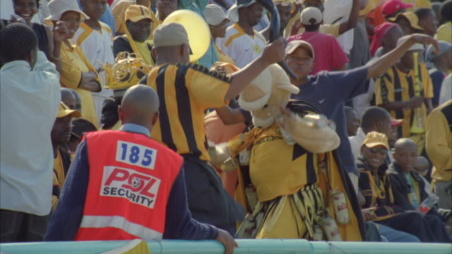vidéos et rushes de zoom in of a kaizer chiefs fan dressed in a yellow bear costume dancing with other fans - dancing bear