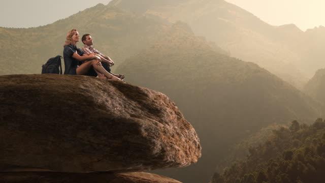 Zoom in of hikers resting on huge rock/Marbella region, Spain