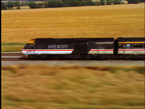 AERIAL zoom in of intercity high speed train through golden countryside / Abingdon, Oxfordshire, England