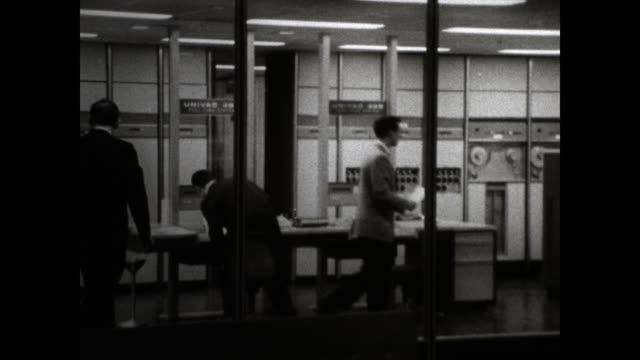 """zoom in of room with glass wall; room full of machines and suited men working; sign with the words """"univac 490"""" - computer stock videos & royalty-free footage"""