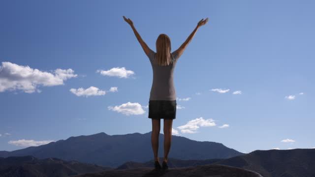 Zoom in of woman lifting her arms in praise/Marbella region, Spain