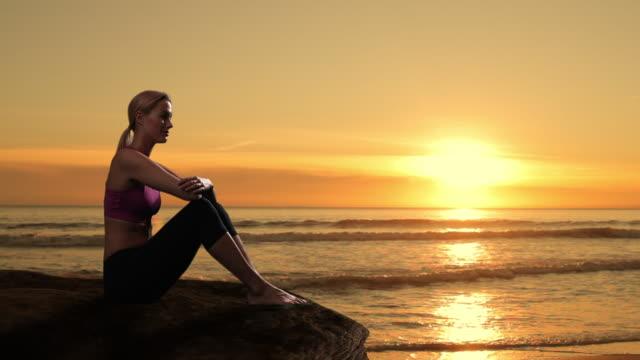 Zoom in of woman sitting on rock beside ocean/Marbella region, Spain