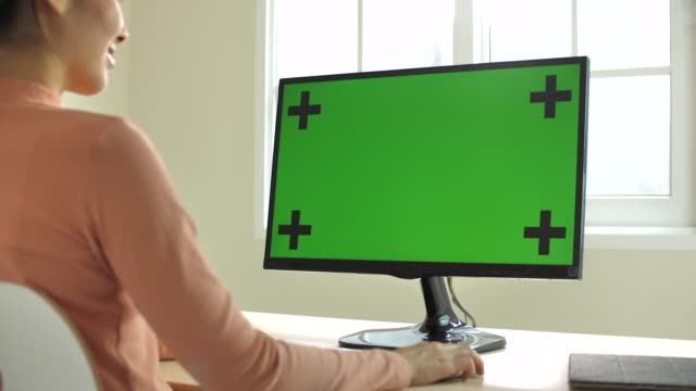 zoom in of young asian woman using computer with green screen at the modern home - microsoft stock videos and b-roll footage