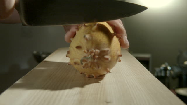 Zoom in on a horned melon being cut in half on a kitchen work surface.