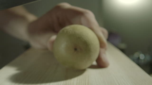 zoom in on a kiwi fruit being cut in half on a kitchen chopping board. - kiwi fruit stock videos and b-roll footage