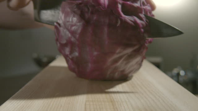 Zoom in on a red cabbage being cut in half on a kitchen chopping board.