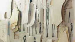 Zoom In On a Wall with Pinned Fashion Drawings and Sketches, Templates Hanging on the Wall.