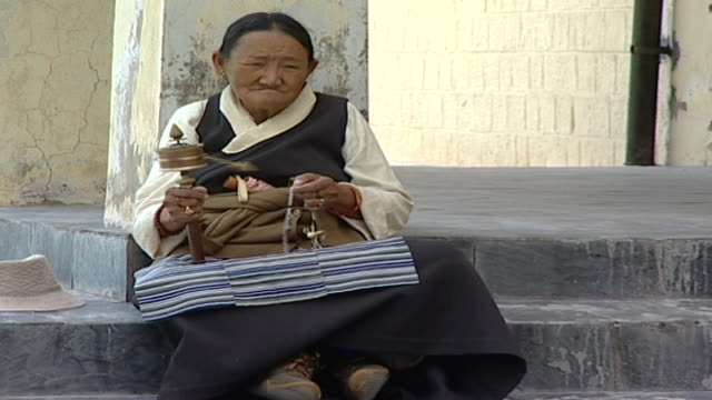 zoom in on an elderly tibetan woman turning a prayer wheel on the steps of the library of tibetan works which holds over 80000 buddhist manuscripts. - traditionally tibetan stock videos & royalty-free footage
