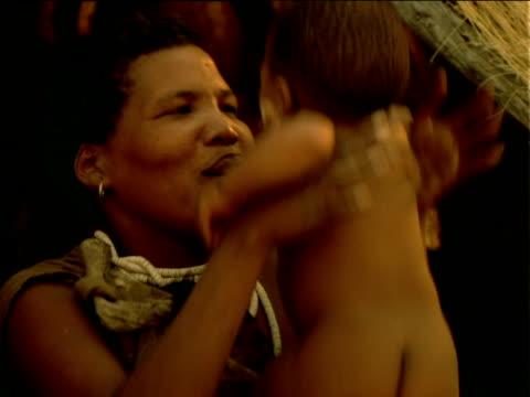 stockvideo's en b-roll-footage met zoom in on basarwa tribeswoman affectionately bouncing her baby - jaar 2000 stijl