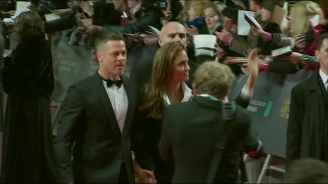 vídeos de stock, filmes e b-roll de zoom in on brad pitt and angelina jolie walking the red carpet of the baftas 2014 - brangelina casal
