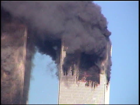 stockvideo's en b-roll-footage met zoom in on burning twin towers with debris and paper falling from windows / zoom out shot from brooklyn / one tower of wtc building with debris and... - geruïneerd