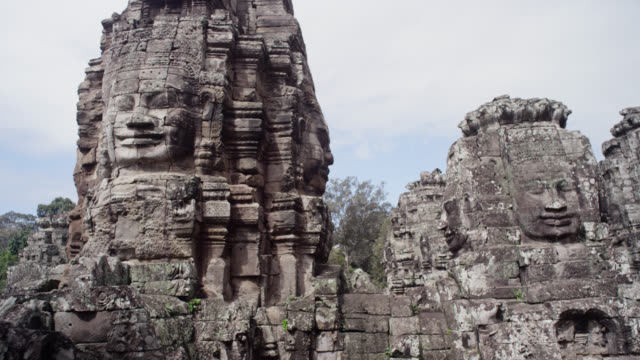 zoom in on carved face, angkor. - carving craft product stock videos & royalty-free footage