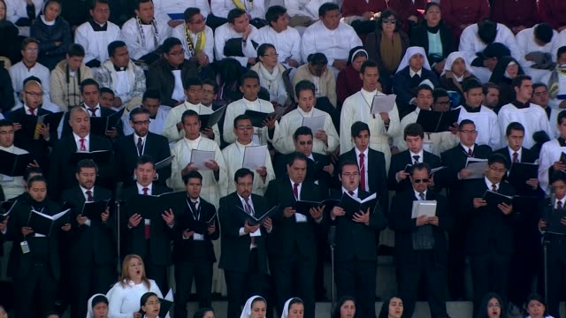 zoom in on chorus singing at ceremony for pope francis in morelia, mexico. chorus holds choir books on stage at venustiano carranza stadium - morelia video stock e b–roll