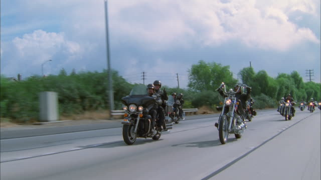 zoom in on group of harley davidson bikers ride pass camera on californian motorway, available in hd. - motorcycle biker stock videos & royalty-free footage
