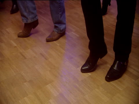 zoom in on male line dancer's denim clad cowboy booted two step shuffle berlin - shuffling stock videos and b-roll footage