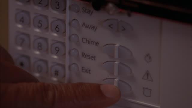vídeos y material grabado en eventos de stock de zoom in on security alarm key pad. man's hand pushes buttons to set it to armed. - equipo de seguridad