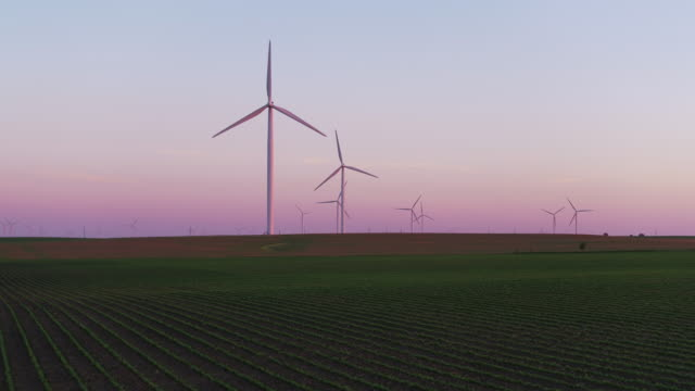 Zoom in on wind farm at sunset