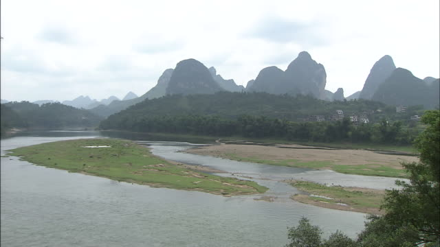 Zoom in over Lijiang River to karst formations.