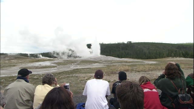 zoom in over tourists watching jets of water and steam erupting from old faithful geyser - old faithful stock videos & royalty-free footage