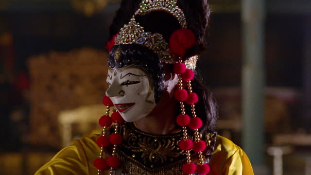 ms zoom in portrait javanese woman wearing traditional mask + costume to close up taking mask off / java - zoom in stock videos & royalty-free footage