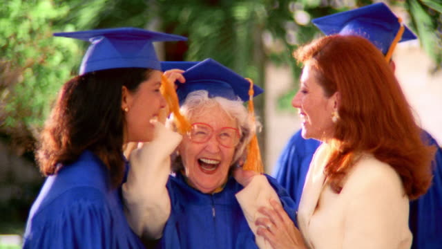 vidéos et rushes de zoom in portrait senior hispanic woman + young woman graduates pose with redheaded woman outdoors / florida - grand mère