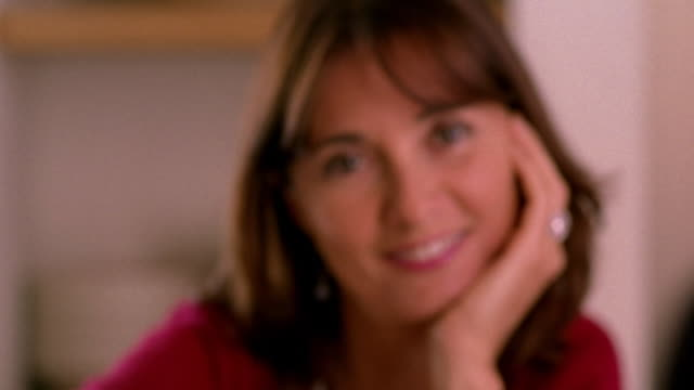 vídeos de stock, filmes e b-roll de zoom in rack focus portrait woman smiling + resting head on hand - só uma mulher madura