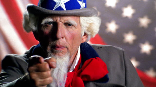 vídeos de stock, filmes e b-roll de zoom in rack focus uncle sam pointing finger at camera / american flag background - apontando sinal manual