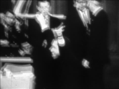 stockvideo's en b-roll-footage met b/w 1968 zoom in richard nixon waving hands in victory sign at republican national convention - vredesteken handgebaar