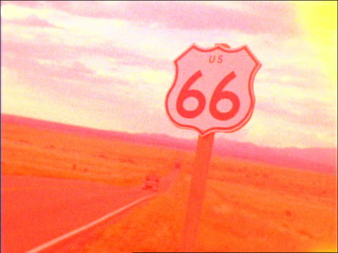 vidéos et rushes de grainy zoom in route 66 road sign on road on grassy plains / flare at beginning - route 66