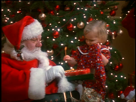 zoom in Santa Claus + small blonde girl playing with toy xylophone near Christmas tree