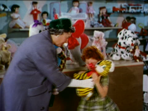 1962 zoom in senior/middle aged woman giving stuffed tiger to young girl in toy store / industrial - toy store stock videos and b-roll footage