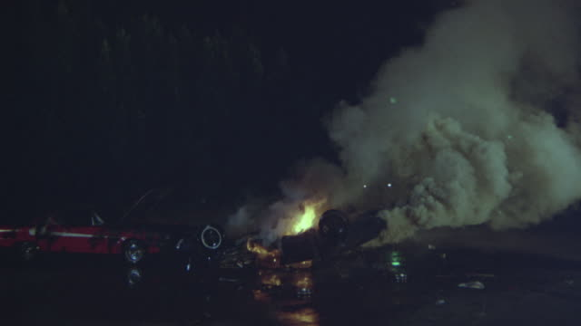 a zoom in shot of a car burning after an accident at night. - road accident stock videos & royalty-free footage
