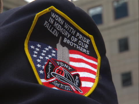 vídeos y material grabado en eventos de stock de zoom in shot of an fire department of new york patch on a firefighter's arm at the 9-11 memorial on the morning of 9/11/11, the tenth anniversary of... - 0 11 months