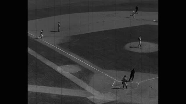 zoom in shot of players playing baseball on field - baseballmannschaft stock-videos und b-roll-filmmaterial