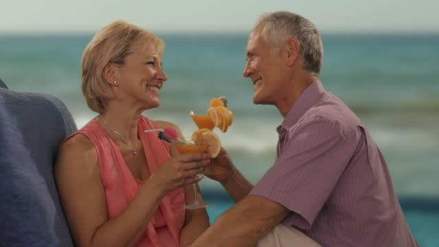 vídeos y material grabado en eventos de stock de zoom in shot of senior couple relaxing by sea with drinks - cóctel tropical