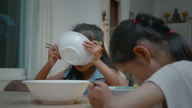 zoom in shot of two asian child girl siblings eating instant noodles and sharing each other for dinner at home with happiness. - other stock videos & royalty-free footage