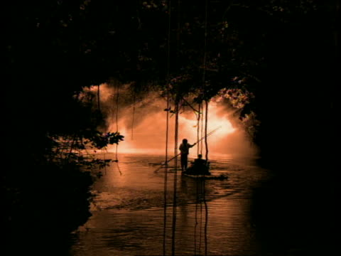 sepia zoom in silhouette man steering person thru mist on raft on river in jungle / jamaica - jamaica stock videos & royalty-free footage