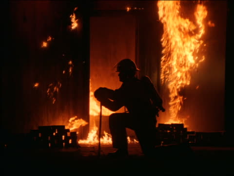 vídeos de stock, filmes e b-roll de ms zoom in silhouette of fireman kneeling in front of burning doorway holding ax - ajoelhando se