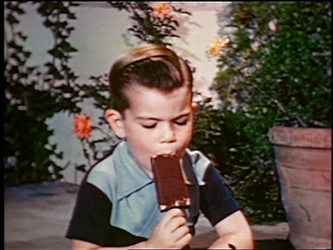 1948 zoom in small boy eating ice cream bar on porch / industrial - ice cream bar stock videos and b-roll footage