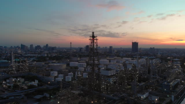zoom in: smoke stack of oil refineries at twilight - oil industry stock videos & royalty-free footage