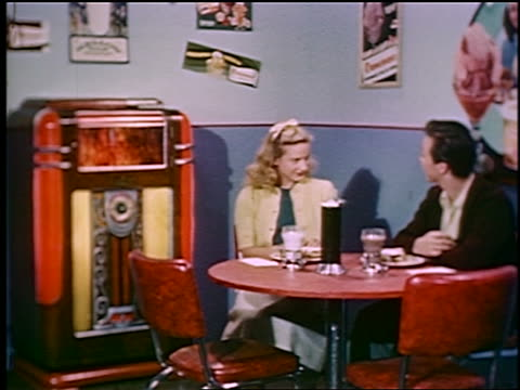 1948 zoom in PAN teen couple drinking milk with meal at table by jukebox in diner / industrial
